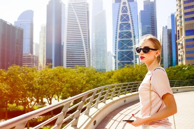 Wind blaast vrouwelijk haar terwijl ze op de brug staat voor mooie wolkenkrabbers van dubai Gratis Foto
