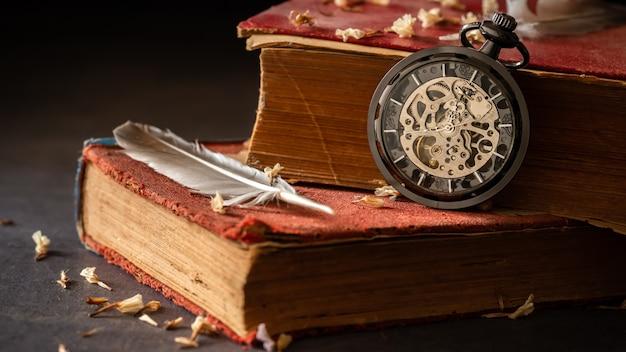 Windend zakhorloge op oude boeken met veren en droge bloembloemblaadjes op de marmeren lijst in duisternis en ochtendlicht. Premium Foto