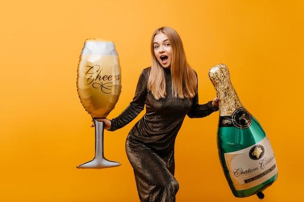 Winderige vrouw met recht kapsel verraste emoties uiten op verjaardagsfeestje. indoor portret van mooie bevallige vrouw met fles champagne en wijnglas. Gratis Foto