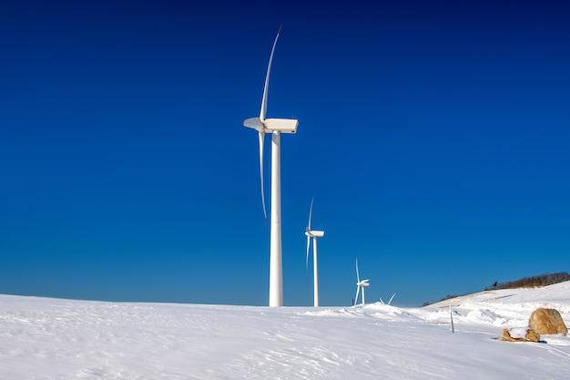 Windturbine en blauwe hemel in winterlandschap Gratis Foto