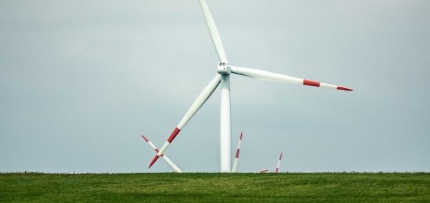 Windventilator die overdag op een groen landschap staat Gratis Foto