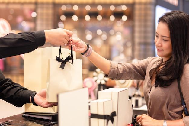 Winkelbediende boodschappentas overhandigen aan vrouwelijke klant. Premium Foto