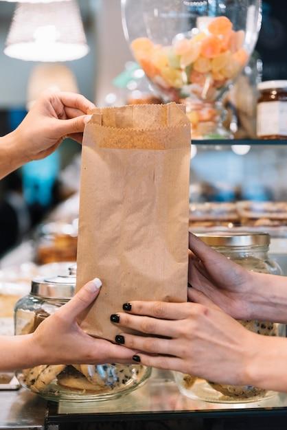Winkelbediende die croissantzak geeft Gratis Foto
