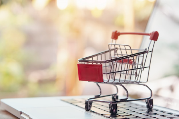 Winkelen online concept. leeg winkelwagentje of trolley op laptop toetsenbord. boodschappenservice op het online web. biedt levering aan huis. Premium Foto