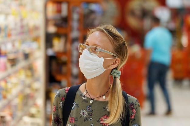 Winkelen tijdens quarantainevrouw die beschermend gezichtsmasker draagt. levensstijl. Premium Foto