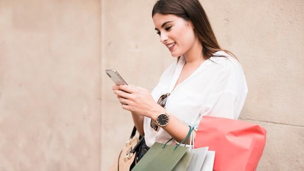 Winkelend meisje dat haar mobiele telefoon met behulp van Gratis Foto