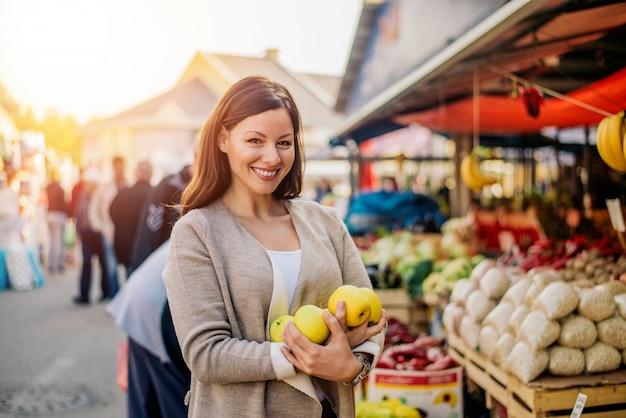 Winkelend vrouw het kopen fruit bij de markt. Premium Foto