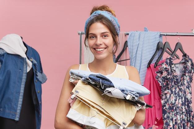 Winkeltijd. blije jonge europese vrouw met hangers met trendy kleding en breed glimlachend, genietend van nieuwsaankopen. gelukkige vrouw die de zomerkleren verzamelt terwijl haar zak inpakt, die gaat reizen Gratis Foto