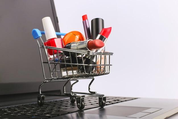 Winkelwagen met cosmetica is op de laptop. online verkoopconcept. Premium Foto