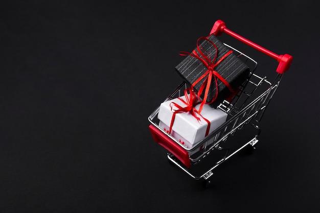 Winkelwagen met geschenken op donkere achtergrond Gratis Foto