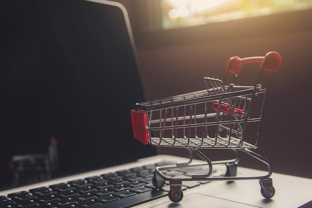Winkelwagen of trolley op een laptop toetsenbord. Premium Foto