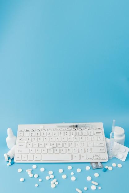 Winkelwagen speelgoed met medicijnen en toetsenbord. pillen, blisterverpakkingen, medische flessen, thermometer, beschermend masker op een blauwe achtergrond. bovenaanzicht met plaats voor uw tekst Premium Foto