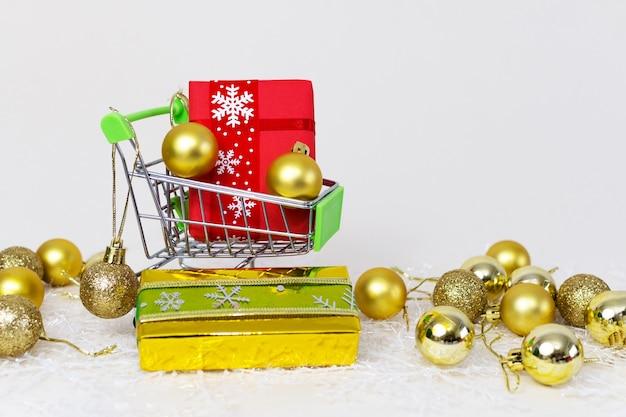 Winkelwagentje met geschenkdozen en gouden bollen op een sneeuwvlok op een witte achtergrond Gratis Foto