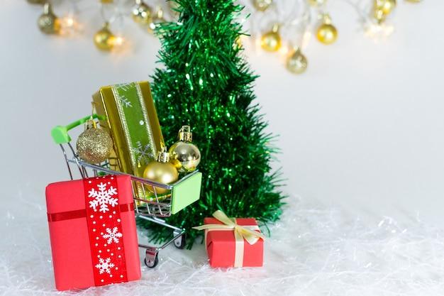 Winkelwagentje met geschenkdozen en gouden bollen op sneeuwvlokken op een witte achtergrond Gratis Foto