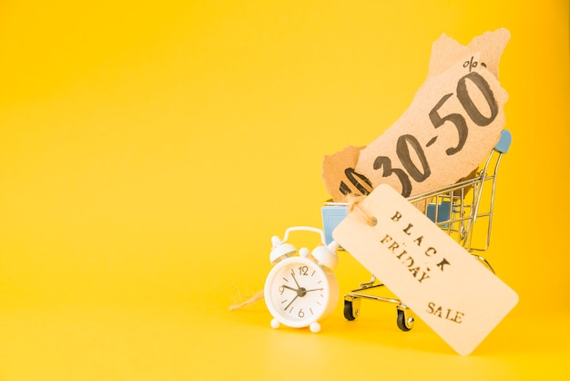 Winkelwagentje met verkoop stukjes papier en tag in de buurt van wekker Gratis Foto