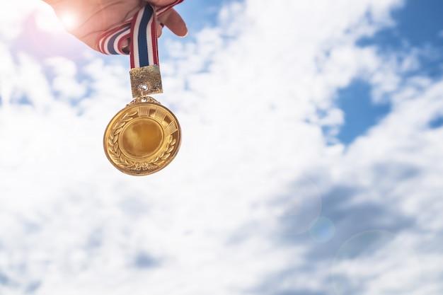 Winnaar hand verhoogd met gouden medailles met thaise lint tegen blauwe hemel. gouden medailles is een onderscheiding Premium Foto