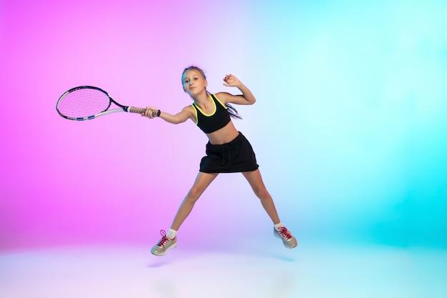 Winnaar. weinig tennismeisje in zwarte sportwear die op gradiënt wordt geïsoleerd Gratis Foto