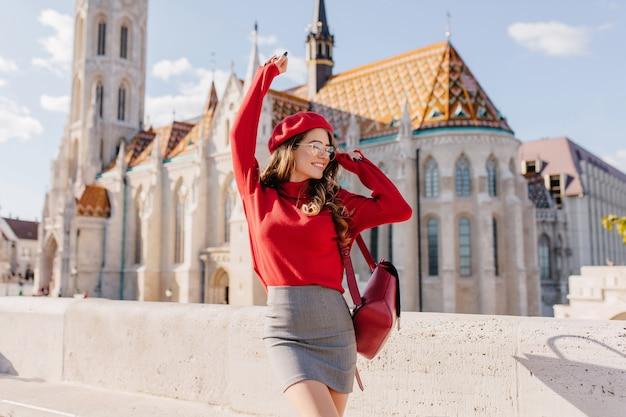 Winnend meisje in grijze rok dansen met blij gezicht expressie met paleis op achtergrond Gratis Foto