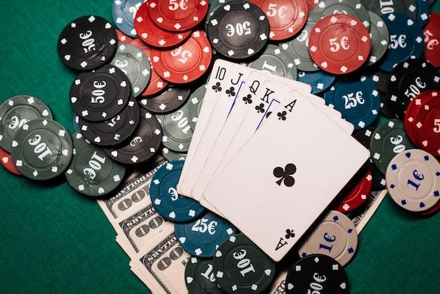 Winnende combinatie van kaarten in casinopoker. royal flush, een heleboel chips en geld dollars Premium Foto