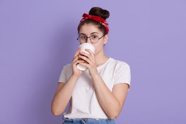 Winsome jonge gelukkig mooie vrouw in rode haarband en wit casual t-shirt, vormt tegen lila ruimte, koffie drinken in papieren beker Gratis Foto