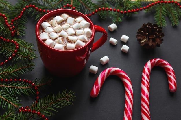 Winter achtergrond met kerstboomtakken, dennenappels, warme chocolademelk, marshmallows, zuurstokken Premium Foto