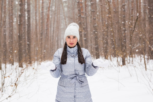 Winter, beauty en fashion concept - portret van een jonge vrouw in jas op besneeuwde natuur muur Premium Foto