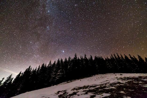 Winter bergen nacht landschap panorama. melkweg helder sterrenbeeld in donkerblauwe sterrenhemel boven donker sparrenbos, zachte gloed aan horizon na zonsondergang. Premium Foto