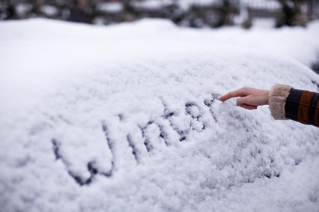 Winter geschreven in sneeuw op auto Premium Foto