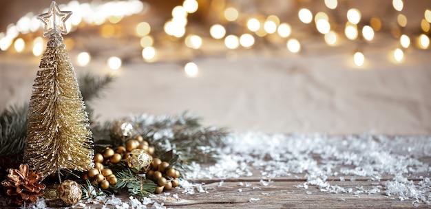 Winter gezellige achtergrond met feestelijke decor details, sneeuw op een houten tafel en bokeh. het concept van een feestelijke sfeer in huis. Gratis Foto