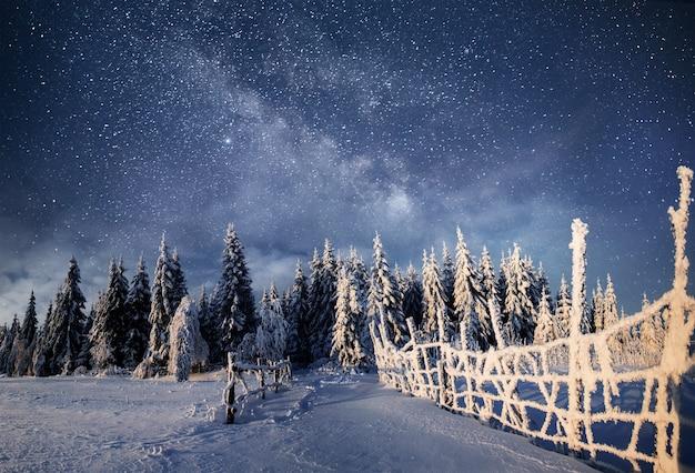 Winter landschap. bergdorp in de oekraïense karpaten. levendige nachtelijke hemel met sterren en nevel en melkweg. deep sky astrophoto. Premium Foto