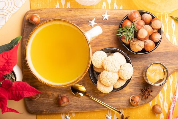 Winter plat met gemberthee, koekjes, noten en kerstversiering op tafel Premium Foto