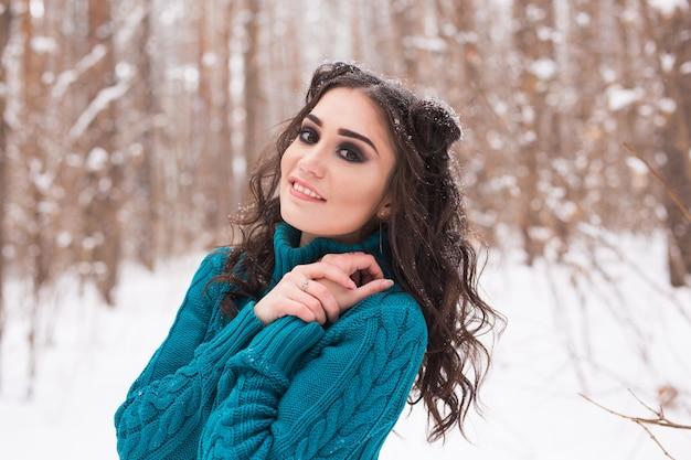 Winter, seizoen en mensen concept - close-up portret van jonge mooie vrouw wandelen in besneeuwde park Premium Foto