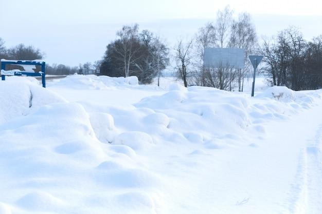 Winter slecht geruimde weg. weg op het platteland dat met sneeuw wordt uitgestrooid. winterlandschap met sneeuwbanken Premium Foto
