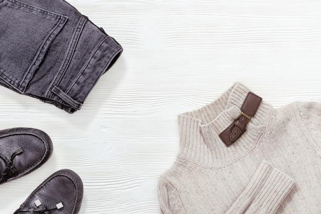 Winter, vallen vrouwelijke kleding. zwart lederen mocassins, donkere jeans en lichtgrijze pullover op witte houten achtergrond met kopie ruimte. plat liggen. Premium Foto