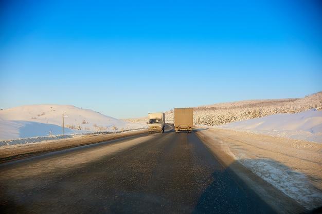 Winter weg in de bergen. de vrachtwagen rijdt langs de weg Premium Foto