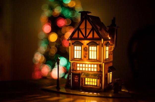 Winterhuis gemaakt van karton gemaakt met hun handen op de tafel, gloeihuis, decoratie voor en kerstmis, kerstboom op de achtergrond, lichten Premium Foto