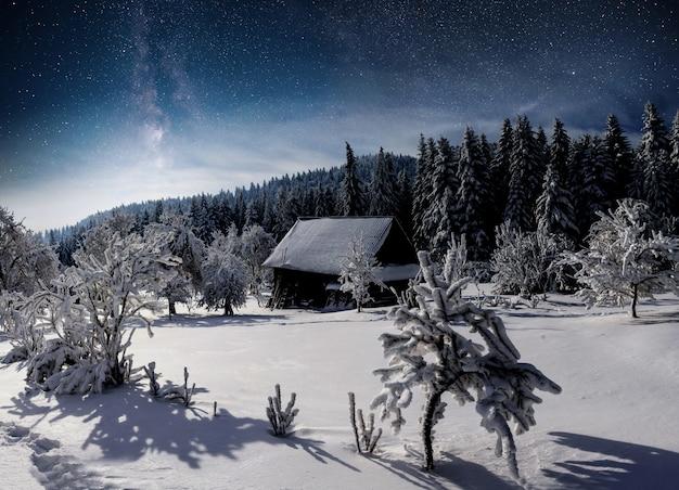 Winterlandschap. bergdorp in de oekraïense karpaten. levendige nachtelijke hemel met sterren en nevel en galaxy. diepe lucht astrofoto Gratis Foto