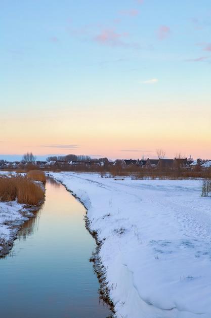 Winterlandschap in nederland met prachtig gekleurde avondrood en verse witte sneeuw Premium Foto