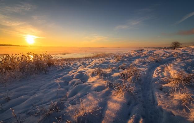 Winterlandschap met sneeuw, oceaan, zee, blauwe lucht, weg, zonneschijn, ijs. Premium Foto