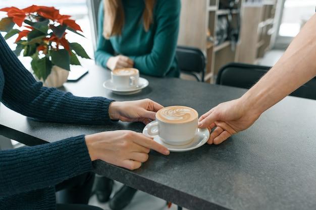 Winterseizoen in de coffeeshop. close-uphand van mensenbarista met kop van kunst coffe Premium Foto