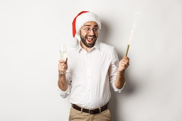 Wintervakantie en feest. opgewonden man vieren oudejaarsavond met vuurwerk schittert en champagne drinken, met kerstmuts, witte achtergrond. Premium Foto