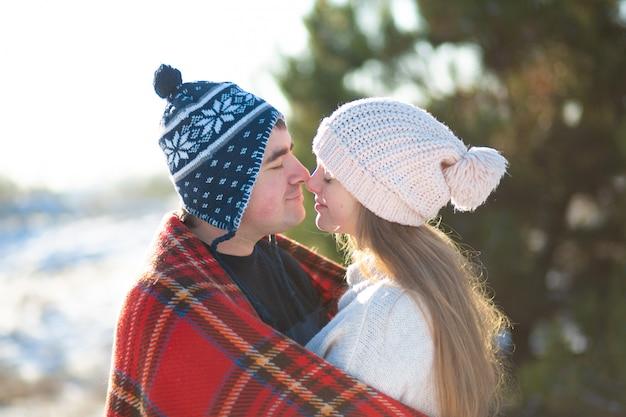 Winterwandeling door het bos. de man met het meisje kuste gewikkeld in een rode geruite plaid Premium Foto