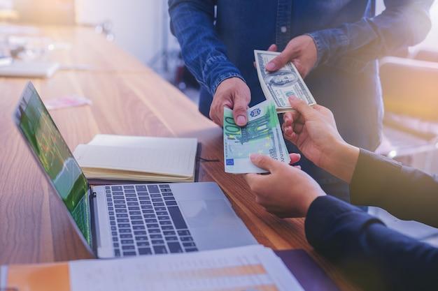 Wissel geld uit, business peoople wissel amerikaanse dollars in voor euro-geld Premium Foto