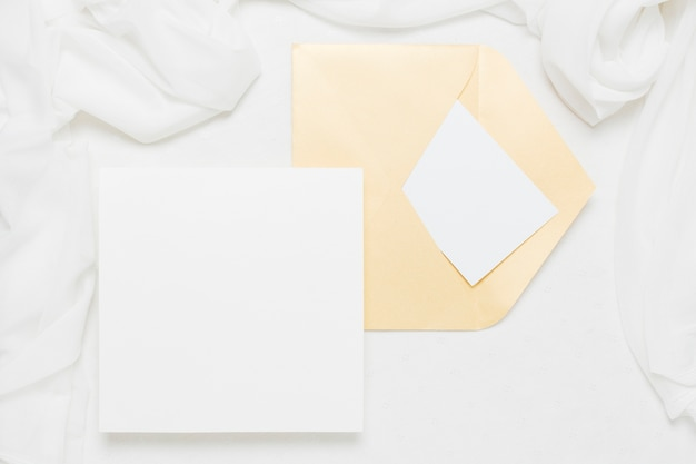 Wit aanplakbiljet dichtbij gele envelop met sjaal op witte achtergrond Gratis Foto