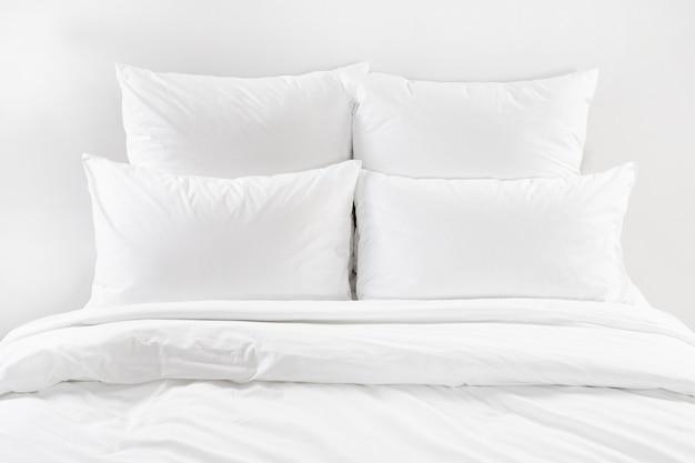 Wit bed geïsoleerd, vier witte kussens en dekbed op een bed Premium Foto