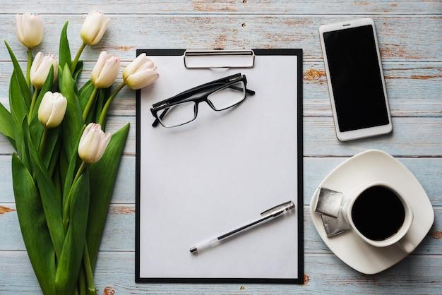 Wit boeket van tulpen met koffiekopje, smartphone en lege laptop Premium Foto