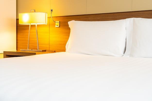 Wit comfortabel kussen en deken op bed met lichte lamp Gratis Foto