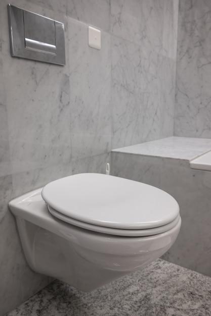 Wit en schoon toilet met de stenen muren in een badkamer Gratis Foto