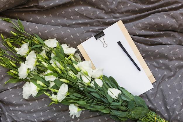 Wit eustoma boeket; klembord en pen op grijze kleding Gratis Foto