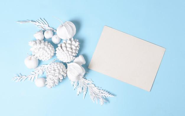 Wit gekleurde dennenappels, takken, physalis bloemen en met lege cadeaubon. plat lag minimaal concept. witte voorwerpen op een blauwe achtergrond. Premium Foto